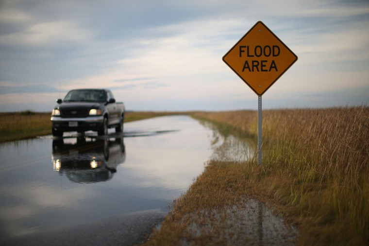 A truck drives on Robbins Road that is flooded from the high tide of the Blackwater River October 9, 2014 in Robbins, Maryland. Several islands and property's located at sea level in the lower Chesapeake Bay region are slowly eroding away as sea levels rise. Officials have projected the sea level will rise several feet over the next century leaving many of the Chesapeake bay's lower islands underwater. (Photo by Mark Wilson/Getty Images)