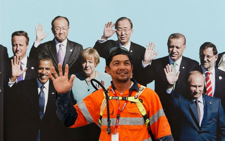 A construction worker has his picture taken in front of a banner with the G20 leaders at Brisbane airport on November 12, 2014 in Brisbane, Australia. World economic leaders will travel to Brisbane for the G20 Leadership Summit November 15-16. (Daniel Munoz/Getty Images)