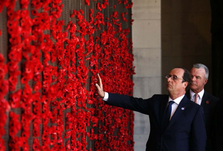 French President Francois Hollande touches the poppies on the Roll of Honour Wall as Director of the Australian War Memorial Brendan Nelson look ons at the Australian War Memorial on November 19, 2014 in Canberra, Australia. French President Francois Hollande is attending meetings in Sydney and Canberra following the G20 Leaders Summit in Brisbane. (Photo by David Gray/Getty Images)