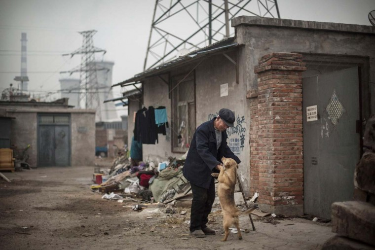 A Chinese man plays with a dog near his home with a coal fired power plant in the background on November 19, 2014 in Beijing, China. U.S. President Barack Obama and China's president Xi Jinping agreed on a plan to limit carbon emissions by their countries which are the world's two biggest polluters at a summit in Beijing last week. (Kevin Frayer/Getty Images)