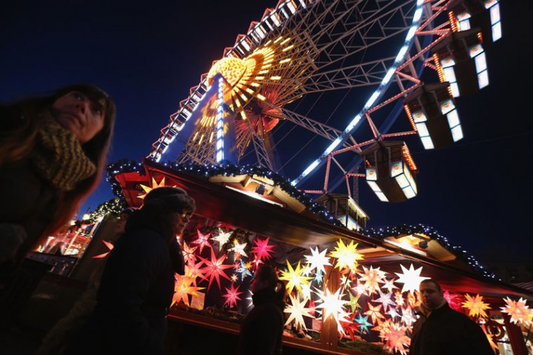 Visitors walk past a stall selling illuminated Christmas stars as a ferris wheel spins overhead at the Christmas market at Alexanderplatz on its opening day on November 24, 2014 in Berlin, Germany. Christmas markets across Germany will open across Germany this week and stay open through the end of December to sell Gluehwein, Christmas decorations, sweets and other delights. (Sean Gallup/Getty Images)
