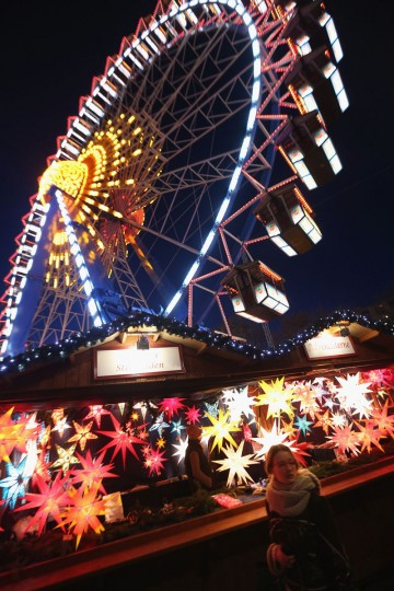 A visitor walks past a stall selling illuminated Christmas stars as a ferris wheel spins overhead at the Christmas market at Alexanderplatz on its opening day on November 24, 2014 in Berlin, Germany. Christmas markets across Germany will open across Germany this week and stay open through the end of December to sell Gluehwein, Christmas decorations, sweets and other delights. (Sean Gallup/Getty Images)