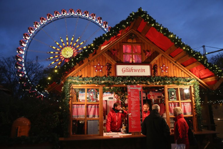 Visitors stop at a stall selling Gluehwein next to an illuminated ferris wheel at the Christmas market at Alexanderplatz on the market's opening day on November 24, 2014 in Berlin, Germany. Christmas markets across Germany will open this week and stay open through the end of December to sell Gluehwein, Christmas decorations, sweets and other delights in an annual tradition. (Sean Gallup/Getty Images)