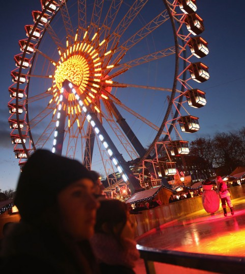 Visitors stand at an ice-skating rink under an illuminated ferris wheel at the Christmas market at Alexanderplatz on the market's opening day on November 24, 2014 in Berlin, Germany. Christmas markets across Germany will open this week and stay open through the end of December to sell Gluehwein, Christmas decorations, sweets and other delights in an annual tradition. (Sean Gallup/Getty Images)