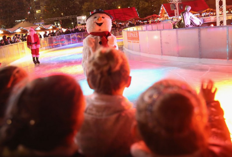 Young visitors wave to a snowman on ice skates at the Christmas market at Alexanderplatz on the market's opening day on November 24, 2014 in Berlin, Germany. Christmas markets will open across Germany this week and stay open through the end of December to sell Gluehwein, Christmas decorations, sweets and other delights in an annual tradition. (Sean Gallup/Getty Images)