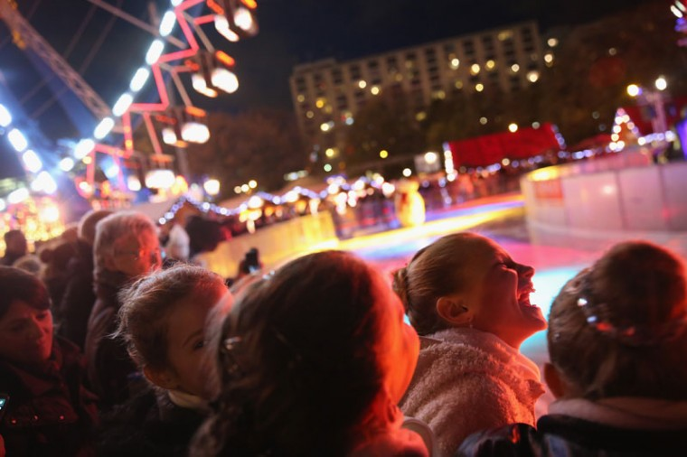 Young girls who were to perform on an ice-skating rink share a laugh at the Christmas market at Alexanderplatz on the market's opening day on November 24, 2014 in Berlin, Germany. Christmas markets will open across Germany this week and stay open through the end of December to sell Gluehwein, Christmas decorations, sweets and other delights in an annual tradition. (Sean Gallup/Getty Images)