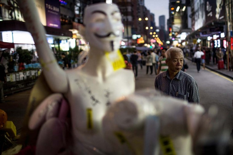 A man looks at mannequins built into a barricade setup by pro-democracy activists on a street in Mong Kok District on November 24, 2014 in Hong Kong. The Mong Kok protest site is scheduled for clearance by baliffs this week after Hong Kong's high court authorized police to arrest protesters who obstruct bailiffs on the three interim restraining orders. (Chris McGrath/Getty Images)
