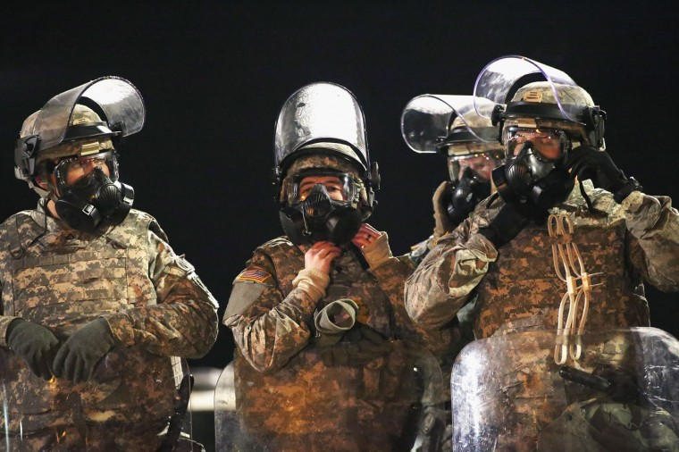 National Guard troops don gas masks while assisting police with controlling demonstrators during a protest in front of the police station on November 25, 2014 in Ferguson, Missouri. Yesterday protesting turned into rioting after the announcement of the grand jury's decision in the Michael Brown case. Brown, an 18-year-old black man, was killed by Darren Wilson, a white Ferguson police officer on August 9. At least 12 buildings were torched and more than 50 people were arrested during the night-long rioting. (Photo by Scott Olson/Getty Images)