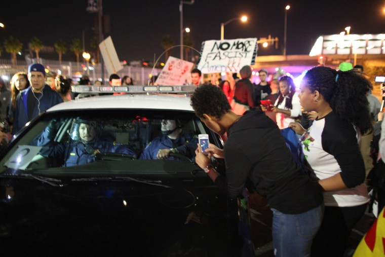 Protesters surround California Highway Patrol officers in their car during a march following the grand jury decision not to indict a white police officer who had shot dead an unarmed black teenager in Ferguson, Missouri on the night of November 25, 2014 in Los Angeles, California. Police officer Darren Wilson shot 18-year-old Michael Brown on August 9, sparking large ongoing protests. (Photo by David McNew/Getty Images)