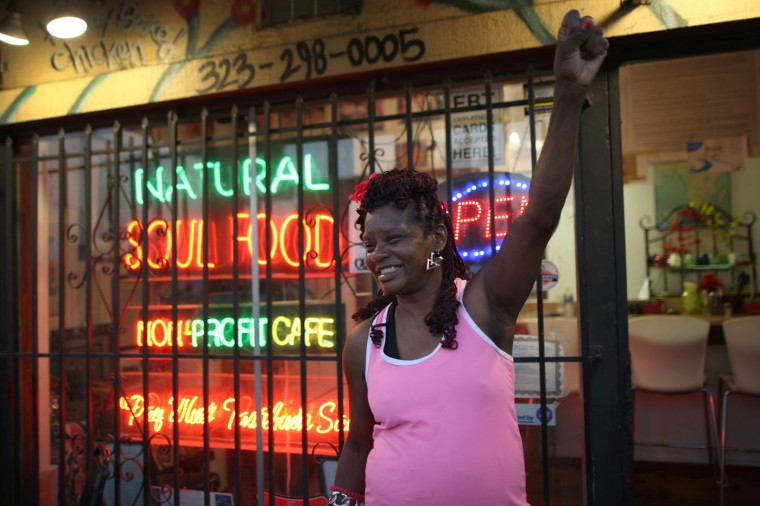 Alexis Watson shows her support for protesters in front of her soul food restaurant during a march following the grand jury decision not to indict a white police officer who had shot dead an unarmed black teenager in Ferguson, Missouri on the night of November 25, 2014 in Los Angeles, California. Police officer Darren Wilson shot 18-year-old Michael Brown on August 9, sparking large ongoing protests. (Photo by David McNew/Getty Images)