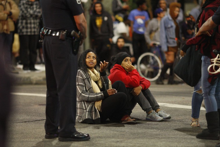Protester sit in the street during a demonstration following the grand jury decision not to indict a white police officer who had shot dead an unarmed black teenager in Ferguson, Missouri in the early morning hours of November 26, 2014 in Los Angeles, California. Police officer Darren Wilson shot 18-year-old Michael Brown on August 9, sparking large ongoing protests. (Photo by David McNew/Getty Images)