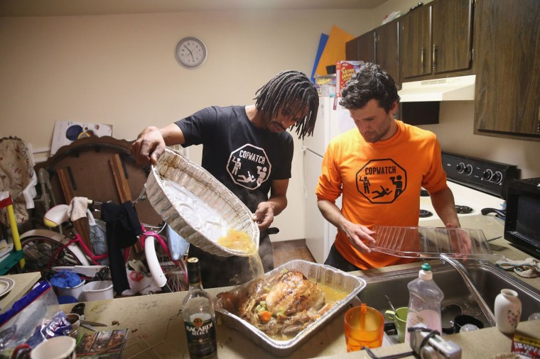 David Whitt (L) and Jacob Crawford prepare a turkey for Thanksgiving dinner on November 27, 2014 in Ferguson, Missouri. Whitt lives in the Canfield Green Apartments near where Michael Brown was killed. Crawford works with Copwatch an organization that monitors police activity in neighborhoods. Whitt started a Copwatch chapter in Ferguson after Brown was killed. The Ferguson area has been struggling to return to normal since the August 9 shooting of Brown, an 18-year-old black man, who was killed by Darren Wilson, a white Ferguson police officer. Monday, when the grand jury announced that Wilson would not face charges in the shooting, rioting and looting broke out throughout the area. (Photo by Scott Olson/Getty Images)