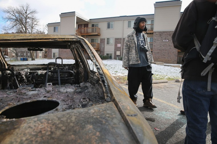 David Whitt, standing next to a burned out car, checks on visitors to the Michael Brown memorial at the Canfield Green Apartments on Thanksgiving Day November 27, 2014 near Ferguson, Missouri. Whitt started a Copwatch chapter in Ferguson to monitor police activity after Brown was killed. The car, which belonged to a journalist, was torched on Tuesday evening. The Ferguson area has been struggling to return to normal since the August 9 shooting of Brown, an 18-year-old black man, who was killed by Darren Wilson, a white Ferguson police officer. Monday, when the grand jury announced that Wilson would not face charges in the shooting, rioting and looting broke out throughout the area. (Photo by Scott Olson/Getty Images)