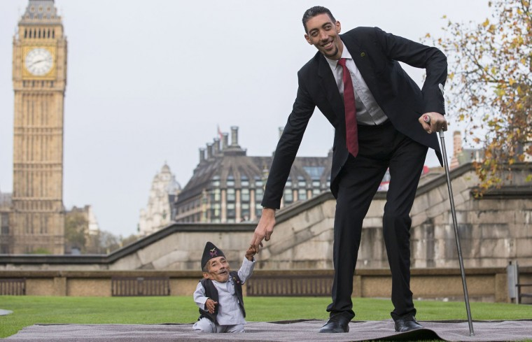 Chandra Bahadur Dangi, from Nepal, (L) the shortest adult to have ever been verified by Guinness World Records, poses for pictures with the world's tallest man Sultan Kosen from Turkey, during a photocall in London on November 13, 2014, to mark Guinness World Records Day. Chandra Dangi, measures a tiny 21.5in (0.54m) the same height as six stacked cans of beans. Sultan Kosen measures 8 ft 3in (2.51m). (Andrew Cowie/AFP/Getty Images)