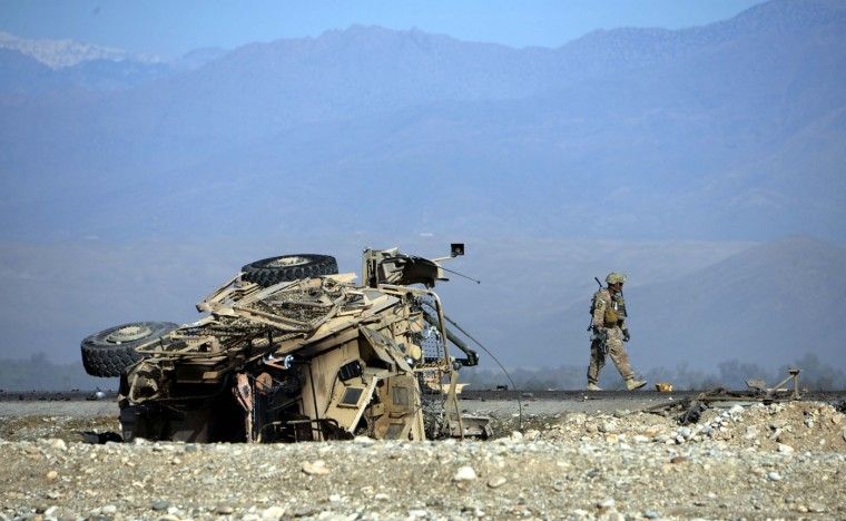 A US soldiers inspects the site of a suicide attack targeting foreign troops in Jalalabad on November 13, 2014. A suicide bomber rammed his explosive-laden vehicle into an armoured vehicle of foreign forces in Jalalabad, the capital of eastern Nangarhar province on November 13, officials said. The attack caused no fatalities to foreign forces or civilians, but damaged an armoured vehicle. (Noorullah Shirzada/AFP/Getty Images)