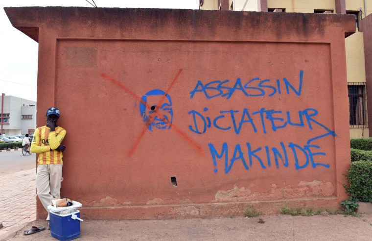 A man stands in front of a wall bearing a graffiti of ousted Burkinabese president Blaise Compaore and reading ''assassin, dictator, Makinde'' on the sidelines of negotiations on the transitional government after the ouster of Compaore in Burkina Faso, on November 12, 2014 in Ouagadougou. The army, which took power after president Blaise Compaore's exit following a popular uprising in response to his bid to extend his 27-year rule, is under heavy international pressure to quickly hand over to a civilian government. (Issouf Sanogo/AFP/Getty Images)
