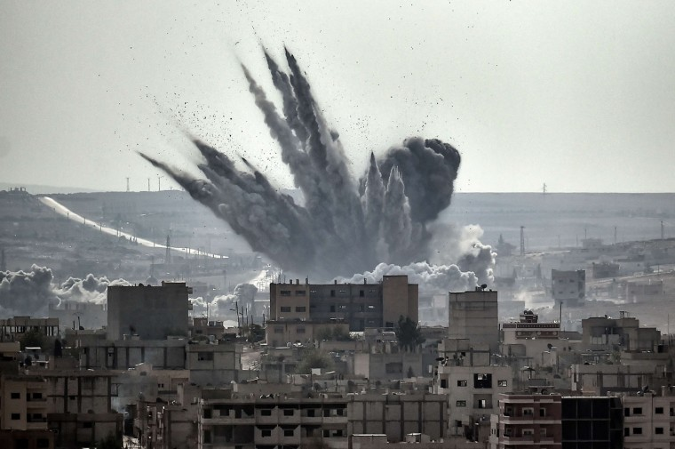 A shell explodes on November 13, 2014 in the Syrian city of Kobane, also known as Ain al-Arab, as seen from the Turkish border village of Mursitpinar, Sanliurfa province. A report issued on November 13 by the Norwegian Refugee Council and International Rescue Committee says Syrians are increasingly unable to escape their country's war as tougher policies in potential host nations are preventing them from taking refuge in the region and beyond. (Aris Messinis/AFP/Getty Images)