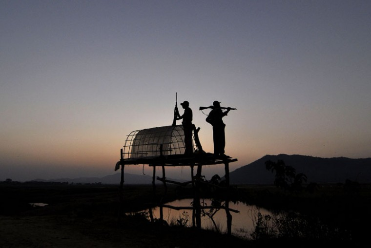 Indian forest guards lookout for rhinoceros from a raised platform at a makeshift camp on the periphery of Pobitora Wildlife Sanctuary in Morigaon district some 50kms from Guwahati on November 18, 2014. The sanctuary, with the highest density of one horned rhinoceros in the world, some 95 according to a 2012 rhino census in an area of just 38.8 sq. km., reopened for tourists from November 2 2014, and has already seen the action of poachers who killed one rhino on November 15, inside the sanctuary and took away the horn. (Biju Boro/AFP/Getty Images)