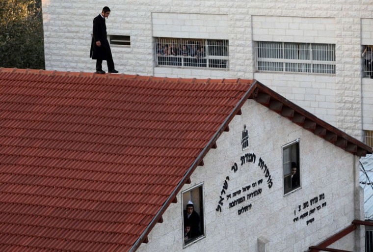 An Ultra-Orthodox man walks on the roof of a building to get a better view of the funeral of Rabbi Moshe Tabersky in Jerusalem, one of the victims of an attack by two Palestinians on Jewish worshippers killing four Israelis at a synagogue in the holy city on November 18, 2014. Two Palestinians armed with a gun and axes burst into a Jerusalem synagogue and killed four Israelis before being shot dead, in the deadliest attack in the city in years. (Gil Cohen-Magen/AFP/Getty Images)