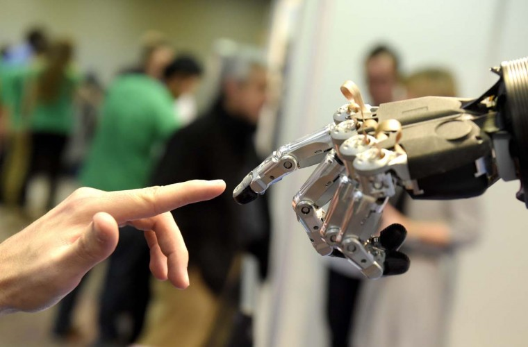 "A man moves his finger toward SVH (Servo Electric 5 Finger Gripping Hand) automated hand made by Schunk during the 2014 IEEE-RAS International Conference on Humanoid Robots in Madrid on November 19, 2014. The conference theme ""Humans and Robots Face-to-Face"" confirms the growing interest in the field of human-humanoid interaction and cooperation, especially during daily life activities in real environments.(Gerard Julien/AFP/Getty Images)"