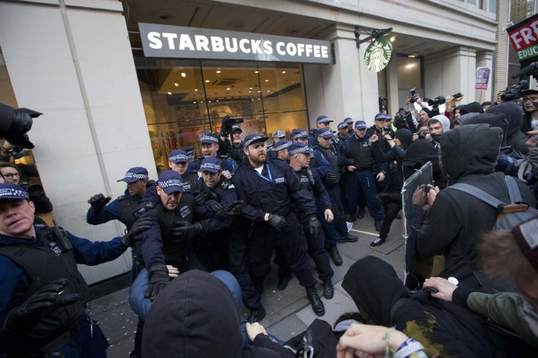 Police officers stand guard outside a Starbucks as they clash with protesters after a march against university fees in London on November 19, 2014. The demonstration organized by the Student Assembly Against Austerity, alongside the Young Greens and National Campaign Against Fees and Cuts demands free education and an end to tuition fees, education cuts and student debt. (Justin Tallis/AFP/Getty Images)