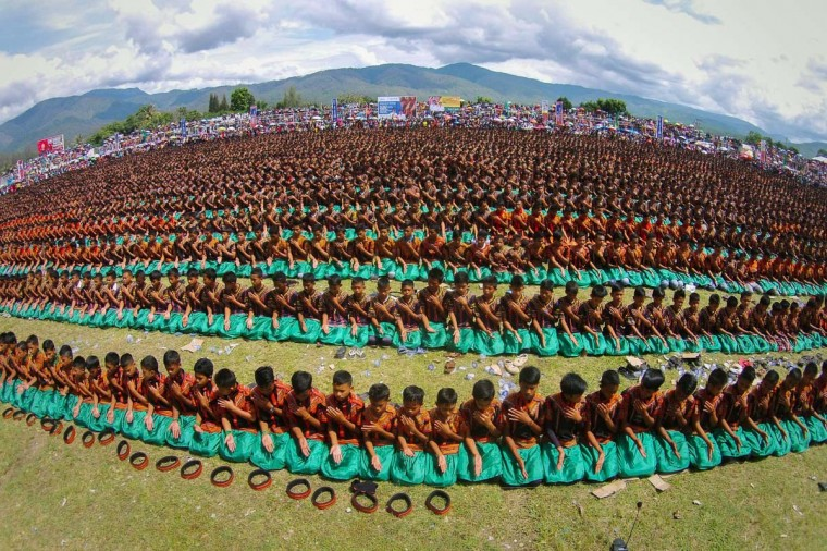 A traditional Saman dance is performed by 5,057 male children and elders belonging to the ethnic Gayo tribe during a ceremony in Gayo Lues highland district in Indonesia's Aceh province on November 24, 2014. The traditional mass dance involving rythmic, syncronized and alternating expressive movement of hands including the upper body without breaking the tight kneeling line formation as they sing verses incorporating religious messages in Gayo language has been categorized in 2011 by United Nations, Educational, Scientific and Cultural Organization (UNESCO) in the list of intangible cultural heritage in need of urgent safeguarding. (Chaideer Mahyuddun/AFP/Getty Images)