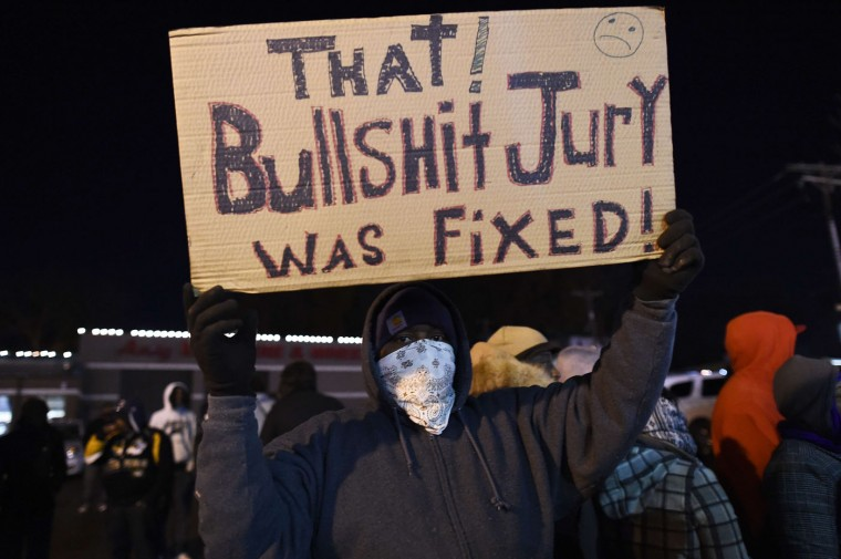 A protester displays a placard in Ferguson, Missouri, on November 25, 2014 during a demonstration a day after violent protests and looting following the grand jury decision in the fatal shooting of a 18-year-old black teenager Michael Brown. Protest marches sprang up in cities across the US on November 25, amid a tense security operation in Ferguson, the Missouri town at the center of the country's latest racially-charged stand-off. Clashes erupted in the St Louis suburb for a second night, after grand jury's decision not to prosecute a white police officer for shooting dead an unarmed black teenager. Jewel Samad/AFP/Getty Images