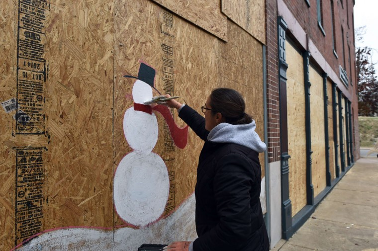 A woman paints a snowman on a boarded window of a store in Ferguson, Missouri, on November 26, 2014. Protest marches sprang up in cities across the US amid a tense security operation in Ferguson, the town at the center of the country's latest racially-charged stand-off following the grand jury decision in the fatal shooting of a 18-year-old black teenager Michael Brown. Clashes erupted in the St. Louis suburb for a second night, after grand jury's decision not to prosecute a white police officer for shooting Brown. Jewel SamadJ/AFP/Getty Images