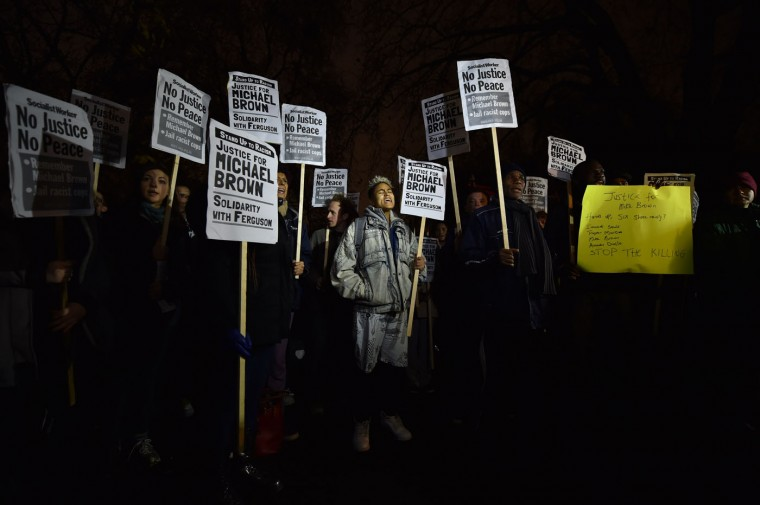 Demonstrators stand and chant with placards during a protest outside the US embassy in London on November 26, 2014 over the US court decision not to charge the policeman who killed unarmed black teenager Michael Brown in the town of Ferguson. The policeman whose killing of unarmed black teenager Michael Brown sparked weeks of riots in the US town of Ferguson will not face charges, the county prosecutor said on November 25, amid mounting anger in the streets. Leon Neal/AFP/Getty Images