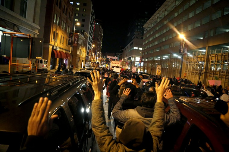"""Protestors put their hands in the air and march through traffic downtown chanting """"Hands up, don't shoot!"""" Tuesday evening. Cassidy Johnson/Baltimore Sun"""