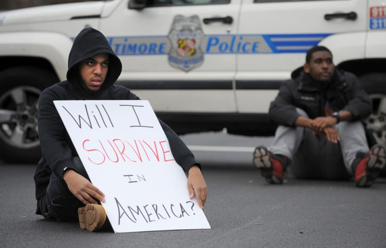 Jimmy Sellers, a Morgan State senior, sits in the intersection of Perring Parkway and Cold Spring Lane during a a rally in Baltimore on Tuesday, Nov. 25, 2014, in the wake of the grand jury decision not to indict officer Darren Wilson in the shooting death of Ferguson, Mo., teen Michael Brown. (Jerry Jackson/Baltimore Sun)