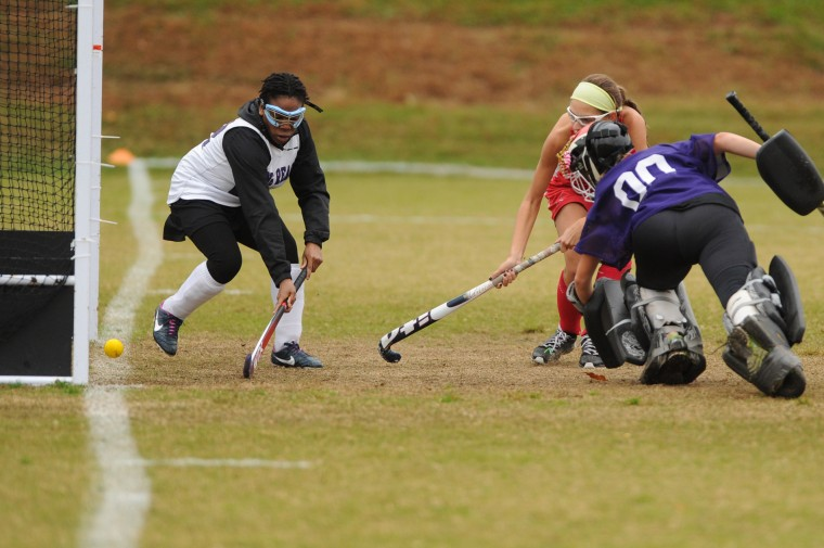 Glenelg's Mia Astran watches as her shot, out of the reach of Long Reach's Kathryn Samuel, left, and goalie Alina Milauskas, crosses the goal line for a second half score during the 3A east reagional field hockey championship game at Long Reach High School on Wednesday, October 29. (Brian Krista/BSMG)