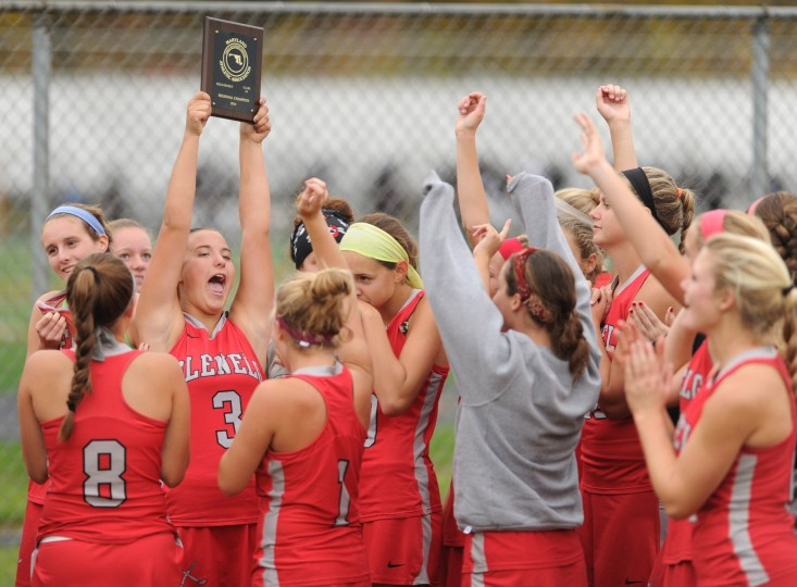 Glenelg's Molly Milani raises the regional championship plaque as she's surrounded by her teammates following their win over Long Reach during the 3A east reagional field hockey championship game at Long Reach High School on Wednesday, October 29. (Brian Krista/BSMG0