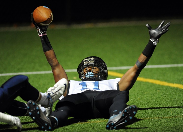 C. Milton Wright's Osiah Walker signals touchdown as he holds the ball in the air and looks for the referee's call after an endzone catch in Thursday night's game at Bel Air. (Matt Button/BSMG)