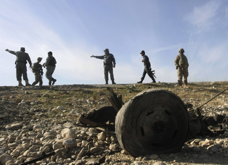 U.S. troops and Afghan policemen inspect at the site of a suicide attack on the outskirts of Jalalabad, November 13, 2014. The suicide bomber rammed his explosive-laden vehicle into U.S. forces travelling in a NATO convoy on Thursday in eastern Nangarhar province; the attack caused no fatalities to foreign forces or civilians, but damaged an armoured vehicle, the provincial spokesman Ahmadzia Abdulzai said, local media reported.(Parwiz/Reuters)