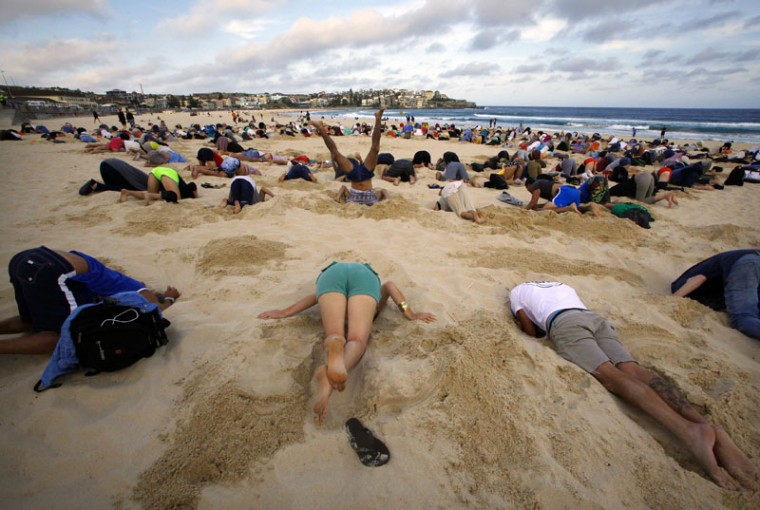 """A group of around 400 demonstrators participate in a protest by burying their heads in the sand at Sydney's Bondi Beach November 13, 2014. Hundreds of protesters participated in the event, held ahead of Saturday's G20 summit in Brisbane, which was being promoted as a message to Australian Prime Minister Tony Abbottís government that, """"You have your head in the sand on climate change"""". (David Gray/Reuters)"""