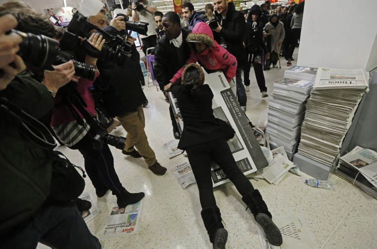 "Shoppers wrestle over a television as they compete to purchase retail items on ""Black Friday"" at an Asda superstore in Wembley, north London November 28, 2014. Britain's high streets, malls and online sites were awash with discounts on Friday as more retailers than ever embraced U.S.-style ""Black Friday"" promotions, seeking to kickstart trading in the key Christmas period. In the United States the Friday following the Thanksgiving Day holiday is called Black Friday because spending usually surges and indicates the point at which American retailers begin to turn a profit for the year, or go ""into the black"". (Luke MacGregor/Reuters)"