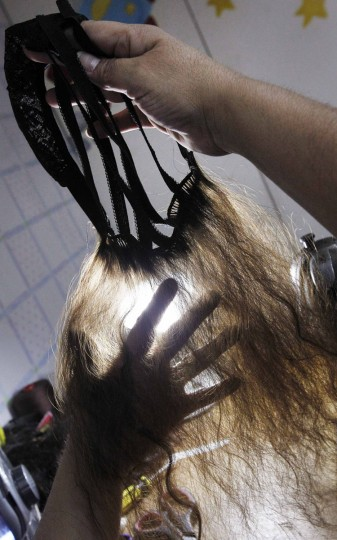 Marcela Reyes holds up a natural hair wig she is making to be donated to a girl undergoing chemotherapy for cancer, in Santiago, August 22, 2014. The wigs, handmade by Italian-Chilean hair stylist Marcelo Avatte and his team, have helped the children regain their self-esteem and confidence during cancer treatment. Renowned for making customized wigs, Avatte has donated more than 300 wigs since 2009 and says he was motivated to begin the project by the pain he felt when his own son lost his hair during chemotherapy. (Rodrigo Garrido/Reuters)