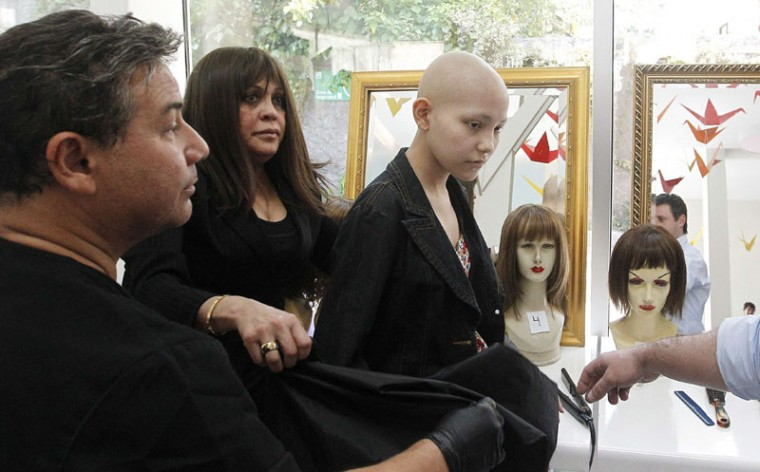 Hair stylist Marcelo Avatte (L) prepares to fit a natural hair wig on Isidora Serrano (R), 14, who lost her hair due to chemotherapy to treat her bone cancer, in the cancer ward of the Luis Calvo Mackenna Hospital in Santiago, October 23, 2014. The wigs, handmade by Italian-Chilean hair stylist Marcelo Avatte and his team, have helped the children regain their self-esteem and confidence during cancer treatment. Renowned for making customized wigs, Avatte has donated more than 300 wigs since 2009 and says he was motivated to begin the project by the pain he felt when his own son lost his hair during chemotherapy. (Rodrigo Garrido/Reuters)