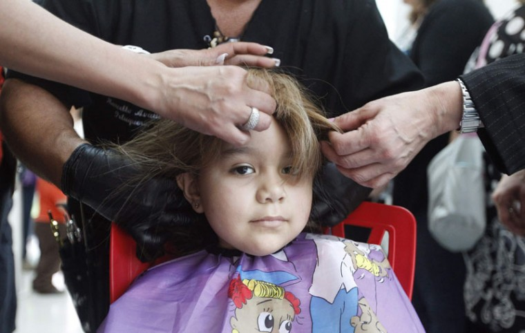 Hair stylist Marcelo Avatte and his team fit a natural hair wig on Alexandra Munoz, 5, who lost her hair due to chemotherapy for a brain tumor, in the cancer ward of the Luis Calvo Mackenna Hospital in Santiago, October 23, 2014. The wigs, handmade by Italian-Chilean hair stylist Marcelo Avatte and his team, have helped the children regain their self-esteem and confidence during cancer treatment. Renowned for making customized wigs, Avatte has donated more than 300 wigs since 2009 and says he was motivated to begin the project by the pain he felt when his own son lost his hair during chemotherapy. (Rodrigo Garrido/Reuters)