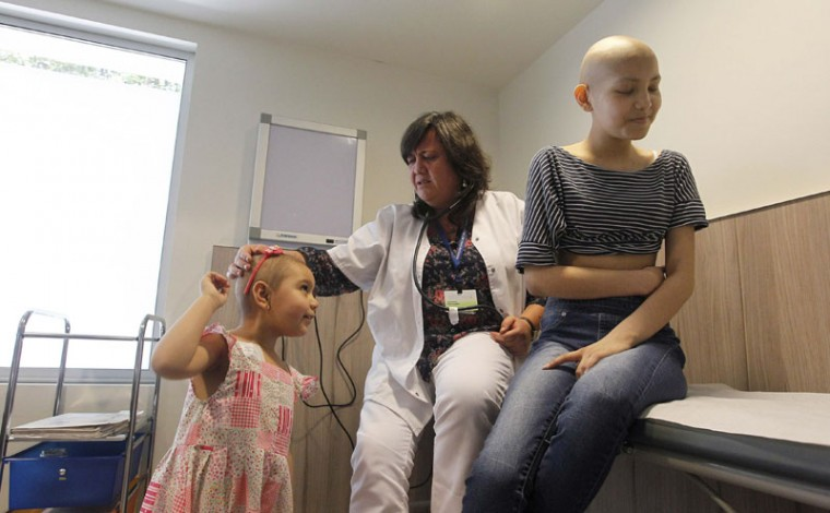 Oncologist Katherine Kopp (C) speaks with her patients Alexandra Munoz (L), 5, and Isidora Serrano, 14, who lost their hair due to chemotherapy to treat their cancers, in the cancer ward of the Luis Calvo Mackenna Hospital in Santiago, October 20, 2014. The wigs, handmade by Italian-Chilean hair stylist Marcelo Avatte and his team, have helped the children regain their self-esteem and confidence during cancer treatment. Renowned for making customized wigs, Avatte has donated more than 300 wigs since 2009 and says he was motivated to begin the project by the pain he felt when his own son lost his hair during chemotherapy. (Rodrigo Garrido/Reuters)