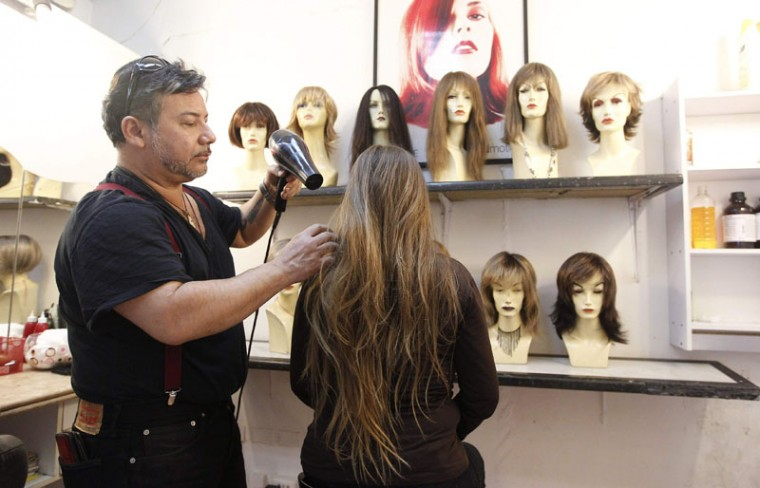 Hair stylist Marcelo Avatte (L) dries the hair of Pamela Matus before she allows him to cut it as a donation for the making of a natural hair wig for a girl undergoing chemotherapy for cancer, in Vina del Mar, August 8, 2014. The wigs, handmade by Italian-Chilean hair stylist Marcelo Avatte and his team, have helped the children regain their self-esteem and confidence during cancer treatment. Renowned for making customized wigs, Avatte has donated more than 300 wigs since 2009 and says he was motivated to begin the project by the pain he felt when his own son lost his hair during chemotherapy. (Rodrigo Garrido/Reuters)
