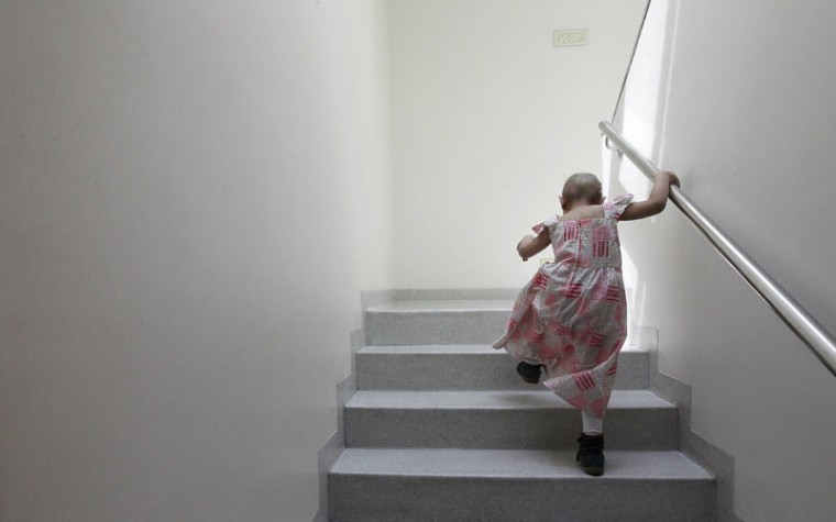 Alexandra Munoz, 5, who lost her hair due to chemotherapy to treat a malignant brain tumor, climbs stairs in the cancer ward of the Luis Calvo Mackenna Hospital in Santiago October 20, 2014. The wigs, handmade by Italian-Chilean hair stylist Marcelo Avatte and his team, have helped the children regain their self-esteem and confidence during cancer treatment. Renowned for making customized wigs, Avatte has donated more than 300 wigs since 2009 and says he was motivated to begin the project by the pain he felt when his own son lost his hair during chemotherapy. (Rodrigo Garrido/Reuters)