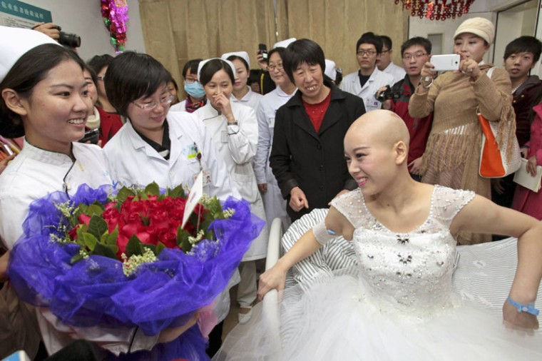 Bride Fan Huixiang (front R), a 25-year-old cancer patient, receives flowers from nurses on her bed before her wedding ceremony at a hospital in Zhengzhou, Henan province November 17, 2014. Fan was diagnosed with late stage adenocarcinoma, a type of cancerous tumor, at her thoracic vertebra this June. She and her 24-year-old husband Yu Haining held their wedding ceremony at the hospital on Monday after five years of relationship, local media reported. (China Daily/Reuters)