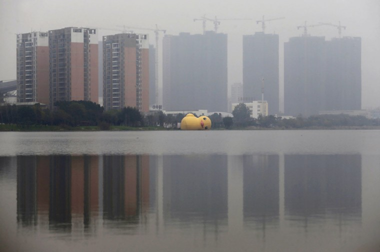 An over-turned inflated rubber duck floats on a lake, in front of a construction site for residential buildings, during a hazy day in Wuhan, Hubei province, November 25, 2014. Gains in property and brokerage stocks led the benchmark indexes in Hong Kong and mainland China higher as investors anticipated a cut in mortgage rates. (REUTERS/Stringer)