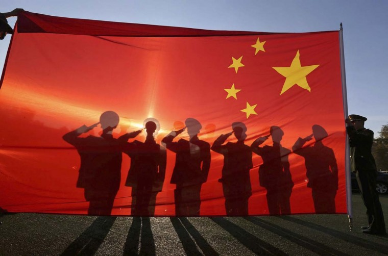Retired paramilitary policemen, who conduct the daily national flag raising and lowering ceremony on Tiananmen Square, salute to a Chinese national flag during a farewell ceremony in Beijing, November 24, 2014. (Reuters)