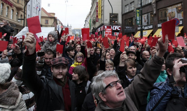 """Demonstrators show symbolic red cards to Czech President Milos Zeman during a protest rally in Prague. Czechs who helped bring about the """"Velvet Revolution"""" that overthrew Kremlin-backed Communist rule are marking the 25th anniversary this week by accusing the country's present-day leaders of once again cosying up to Russia. The focus of their anger is President Milos Zeman, who has taken a pro-Russian line on economic sanctions and described Pussy Riot, the punk group jailed for blasting out a song denouncing President Vladimir Putin in a Moscow cathedral, as hooligans who should not have been treated as political prisoners. The Czech Republic marks the anniversary of the 1989 Velvet Revolution, which led to the fall of the communist regime 25 years ago, on Monday. (David W Cerny/Reuters)"""
