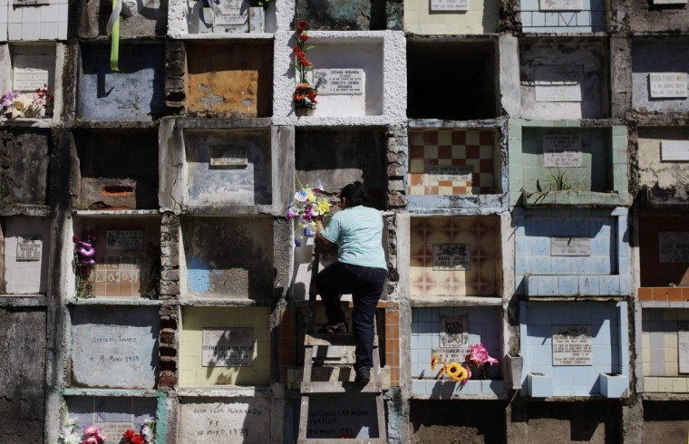A woman climbs a ladder to place flowers on the crypt of a family member during the Day of the Dead at a cemetery in Panchimalco, on the outskirts of San Salvador. Catholics honor their dead on November 1 and 2 by cleaning and decorating the graves with flowers and spending time next to the graves of their deceased beloved ones. (Jose Cabezas/Reuters)