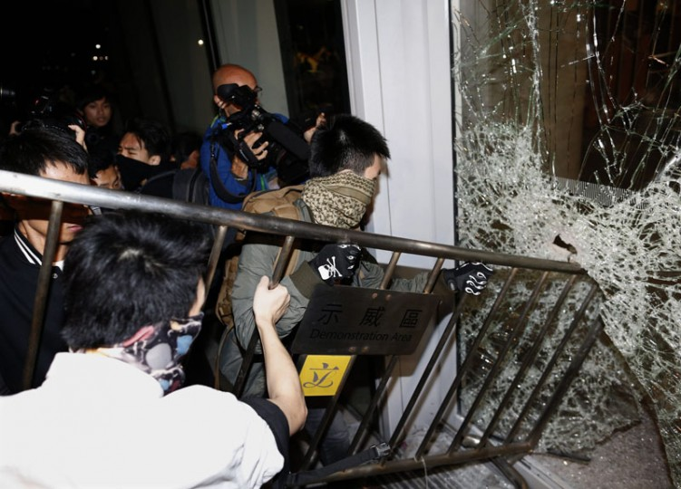 "Masked pro-democracy protesters try to break with a fence a glass window of the Legislative Council in Hong Kong early November 19, 2014, in response to an earlier clear up of part of the ""Occupy Central"" protest site. Hong Kong on Tuesday cleared part of a protest camp in the heart of the city that has been occupied by pro-democracy demonstrators for nearly two months, leaving most of the main protest site intact. (Tyrone Siu/Reuters)"