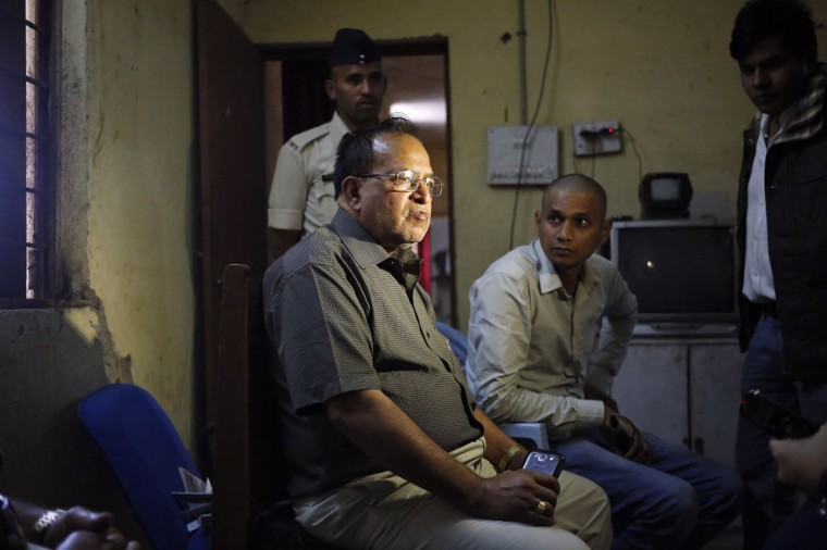 "R.K.Gupta (L), a doctor who performed sterlisation surgeries at a government mass sterilisation ""camp"", sits at a police station as police and the media look on in Bilaspur, in the eastern Indian state of Chhattisgarh, November 13, 2014. Gupta, whose sterilisation of 83 women in less than three hours ended in at least a dozen deaths said on Thursday the express operations were his moral responsibility and blamed adulterated medicines for the tragedy. Gupta, who says he has conducted more than 50,000 such operations, denied that his equipment was rusty or dirty and said it was the government's duty to control the number of people that turned up at his family-planning ""camp"". (Anindito Mukherjee/Reuters)"